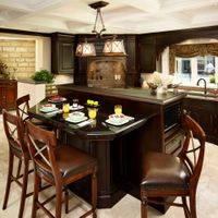 This open concept kitchen featuring maple-espresso cabinets and quartz countertops with a  granite breakfast bar, create cooking and eating areas divided by a bronze capped knee wall.