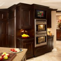 Built-in appliances such as this double wall oven, freezer, and TV also keep the area organized.