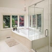 Want your bathroom to appear larger? Consider dressing your walls the same as your floor. This particular ensuite uses white porcelain tiles. For additional visual interest, the tub skirt is finished to match the vanity cabinets.
