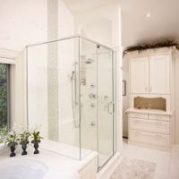 Even when remodelling in neutral tones, every room needs an accent piece. This large, clear glass shower uses a glass tile strip that is subtle, yet eye-catching.