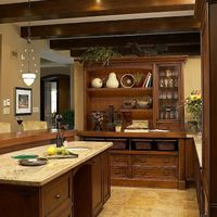 Stained cherry beams, set above lightly stained cherry cabinets on a limestone floor, create a real timeless look.