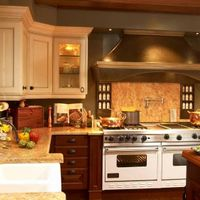 Painted upper cabinets paired with stained base and island cabinets are reflected in other materials in the room. A richly finished copper hood brings additional lustre to the room.