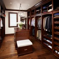This stunning walk-in closet is beautifully finished in Honduras Mahogany. All items are well organized and readily accessible thanks to the open concept design. The centre island provides even more storage and a place to relax.