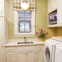Keep your laundry room looking fresh by choosing white or off-white cabinets, paired with equally clean looking Corian countertops.