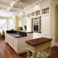 Classical detailing and finishes complete this off-white kitchen, from floor to beamed ceiling. Rich walnut floors with custom cabinets and brushed black granite countertops add contrast throughout.