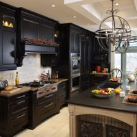 Dare to go dark? With proper light from various sources, darker kitchens such as this rubbed black and painted island millwork, showcase a very dramatic scene.