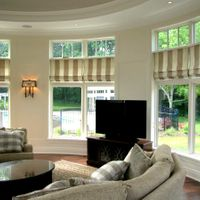 High domed ceilings and large windows in this round living room create a welcoming, spacious atmosphere. Roman style blinds provide privacy when needed.
