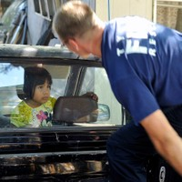 A young girl watches as a Tyler firefighter climbs into the back of a pickup Monday, Sept. 21, 2015, while attempting to extract her from the locked vehicle in Tyler, Texas. The girl reportedly locked herself in the passenger compartment of the truck and either couldn't or wouldn't unlock the door. Firefighters had to break the drivers side window to free the girl from the truck unharmed.