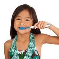 YOUNG ASIAN GIRL BRUSHING TEETH