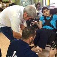 Helping adjust a wheelchair to a Jordanian youth