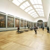 A modern museum with large paintings hanging on each wall
