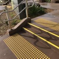 Small external stair way in a primary school with a double handrail on each side, yellow tread nosing strips and yellow tactile ground surface indicators on each landing