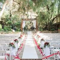 redwood room calamigos ranch wedding ceremony decor red and white floral aisle petals