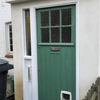 New door frame for porch with reclaimed front door and double glazed side light.
