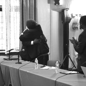 Dr. Cornel West embraces Kendrick Kemp after giving his presentation at his final thesis project.