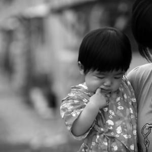 "July, 2012. A mother of two stands in front of her ""temporary home"" holding her youngest. The family was displaced from nuclear radiation and they lived in Shinchimachi's temporary housing for four years."