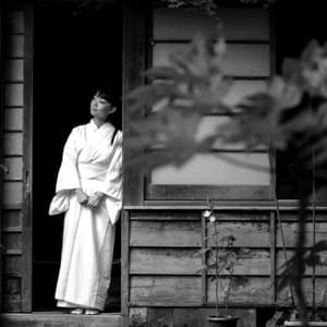 "The caretaker of a Shinto shrine in Soma, Fukushima looks out from her home. The Great East Japan Earthquake and the Fukushima Daiichi Nuclear Disaster instantly brought ""Fukushima"" to the global scene, making the name infamous. Here a child's eyes well with tears from the bitter cold during a free concert for disaster victims in put on in Shinchimachi by Japan's famous AKB48 band in November, 2011. Shinchimachi is known for heavy winds that keep the village cold in the winter, cooler in the summer, and are thought to have blown away radioactive nuclides when the power plant exploded."