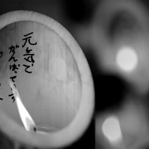 "A candle inside of bamboo reads, ""元気でがんばってます安らかに"" (I am fine and living my life to the fullest. So rest in peace) at an annual memorial in Shinchimachi for victims of the March, 2011 disaster. Large scale disasters have shaped public memory through symbolic meanings and iconic images, while the places, objects and people are forever negatively marked because of them (Gamson, 1988; Hariman & Lucaites, 2003). The Fukushima nuclear disaster was large in scale, and gained extensive global media attention that it will likely be fused in public memory."