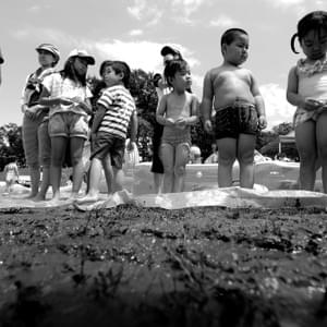 Children play outside in the mud during Shinchimachi's summer festival. The day before the festival the park had it's top layer of grass and dirt removed in an attempt to lower the ground radiation. Still, they play in the mud.