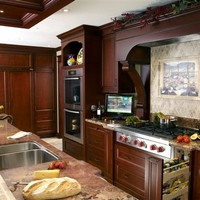 A deep cherrywood finish complements the natural reds in the granite countertop which is accentuated by a stone backsplash.