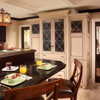 Custom cabinetry designed to conceal refrigeration and align with lighting features also provides practical storage space.