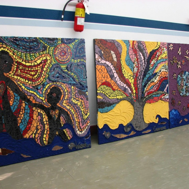 Three of eight panels of the Jamie Oliveria created stories with the students of the School by the River.