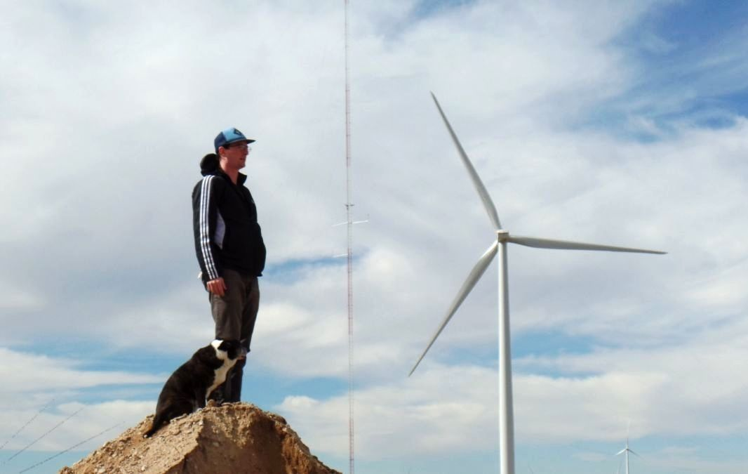 """Nathanael (aka """"Don""""), with his dog Sancho, reflects momentarily in front of a wind turbine in CO, 10.2014. CLICK PHOTO TO SUPPORT"""