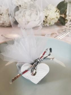 Organza wrapped almond dragées with a handmade porcelain lace embossed charm, tied with Liberty ribbon