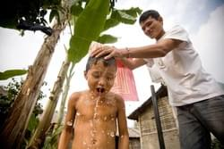 """Aiya!"" Binay yelps while being bathed by his father in cold water outside their hut. The family's life is a simple one, aside from their two room hut and some pots and pans their only other possession is the bike with which Pema travels to the nearby town. Because the refugees have no citizenship, they are unable to work. Twice Pema and his older brother left the camp to neighboring India to work illegally and supplement the rations provided to his family."