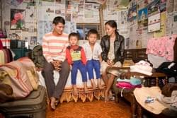 Pema (left to right) his sons Bishal, 6, Binay, 7, and wife Jasoda, 26, in their family's hut.