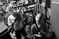 While searching through a storage closet, Dalton and his brother Clay, 9, pick up and handle a couple of shotguns.