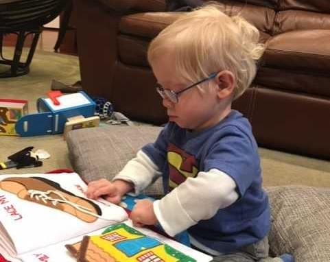 Toddler with glasses looking at a book.