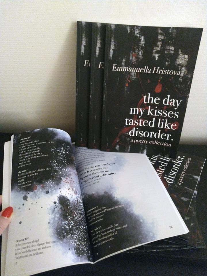 Hand opening a full-color paper back copy of The Day My Kisses Tasted Like Disorder by Emmanuella Hristova in front of other copies of the book
