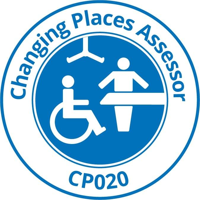 "The Changing Places Logo, with a pictogram of a wheelchair user, next to an adult-sized change table and a person standing next to it. The is an overhead ceiling hoist too. Over the logo, it says ""Changing Places Assessor""."