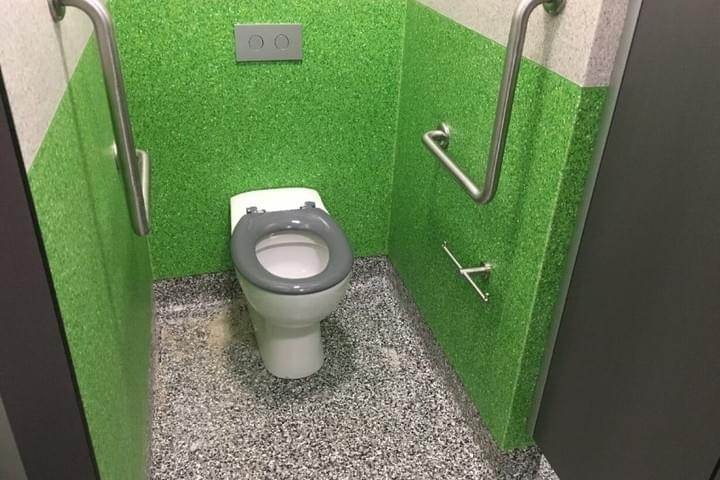 A view inside an ambulant toilet cubicle, showing the toilet pan, grabrails, grey seat and toilet roll holder
