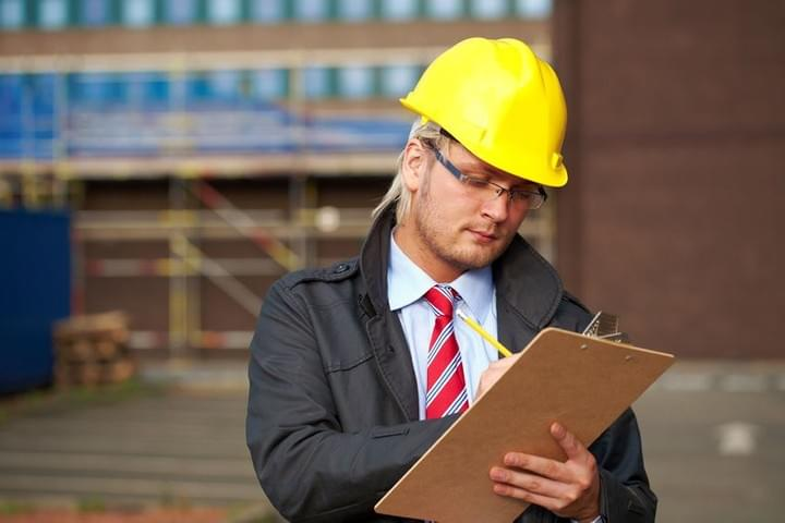 A male access consultant is on a building site, wearing a hardhat and using a clip board to take notes