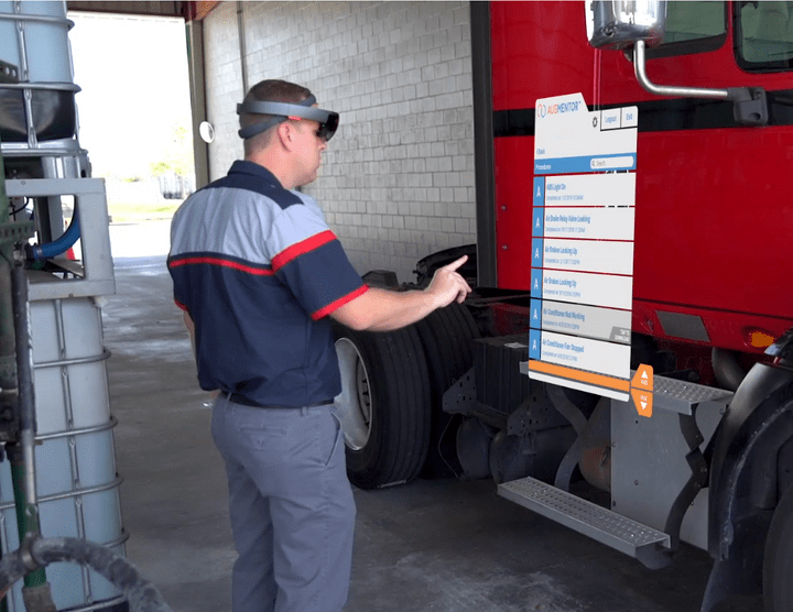 Trucking mechanic using AR software to fix a problem