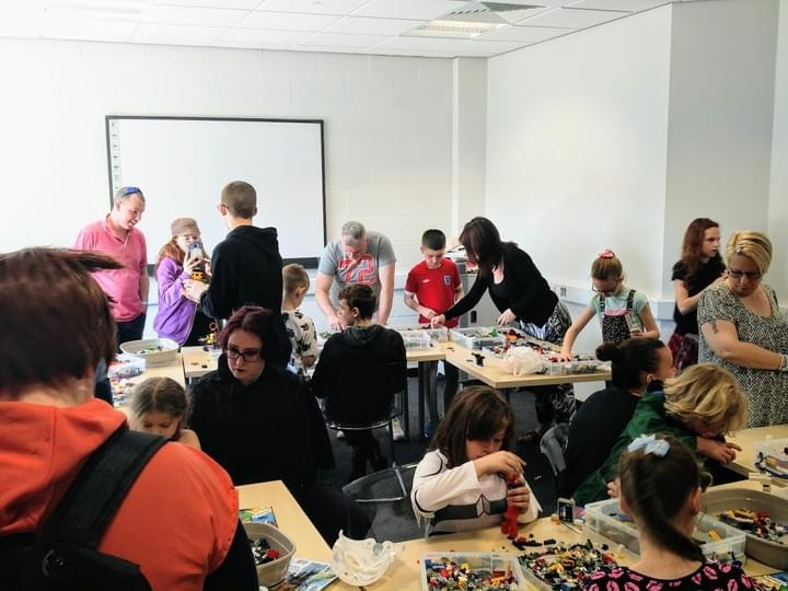 A room full of LEGO builders at a community event