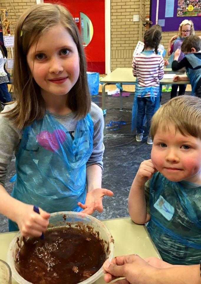 Two children take part in a bake off preparing a chocolate cake