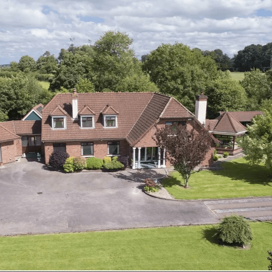 Colbert & Co Estate agents are delighted to present this magnificent 6 bedroom home to the open market. Located on the edge of the North Cork village Rathcormac, this Brideview built home has a huge amount to offer its new owner. From the sweeping driveway through the 1 acre of manicured gardens to the rear workshop there is something for everyone. The Jack Lynch tunnel is only 20 mins drive away and the nearby village a good stride of a walk meaning you have the peace and quiet of the countryside yet not too far to travel should you need the milk!   On entering the property you have large pillars with a sweeping road which leads up the beautiful red brick facade. Through the entrance you are greeted with an open plan design which was ahead of its time back in late 90s. A large hallway with staircase leading to 1st floor catches your eye before leading you into the huge living space with open fire and raised kitchen area which looks over the room. Off the kitchen is a sunroom which is full of light and where the owners live to reside. The doors off the sunroom lead you the magnificent rear garden which has a BBQ area, floral covered walkway and a pedestrian access.
