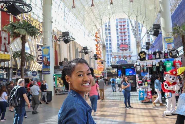 Woman smile at the Fremont Street Experience in the daytime in a protective hairstyle