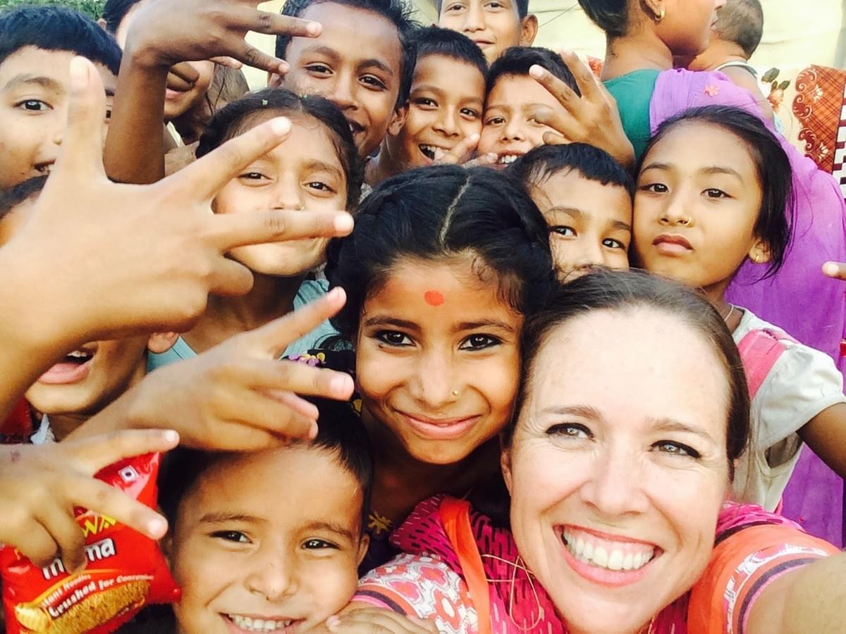 Sarah Davison-Tracy, founder of Seeds of Exchange, visits with children in a village in far western Nepal.