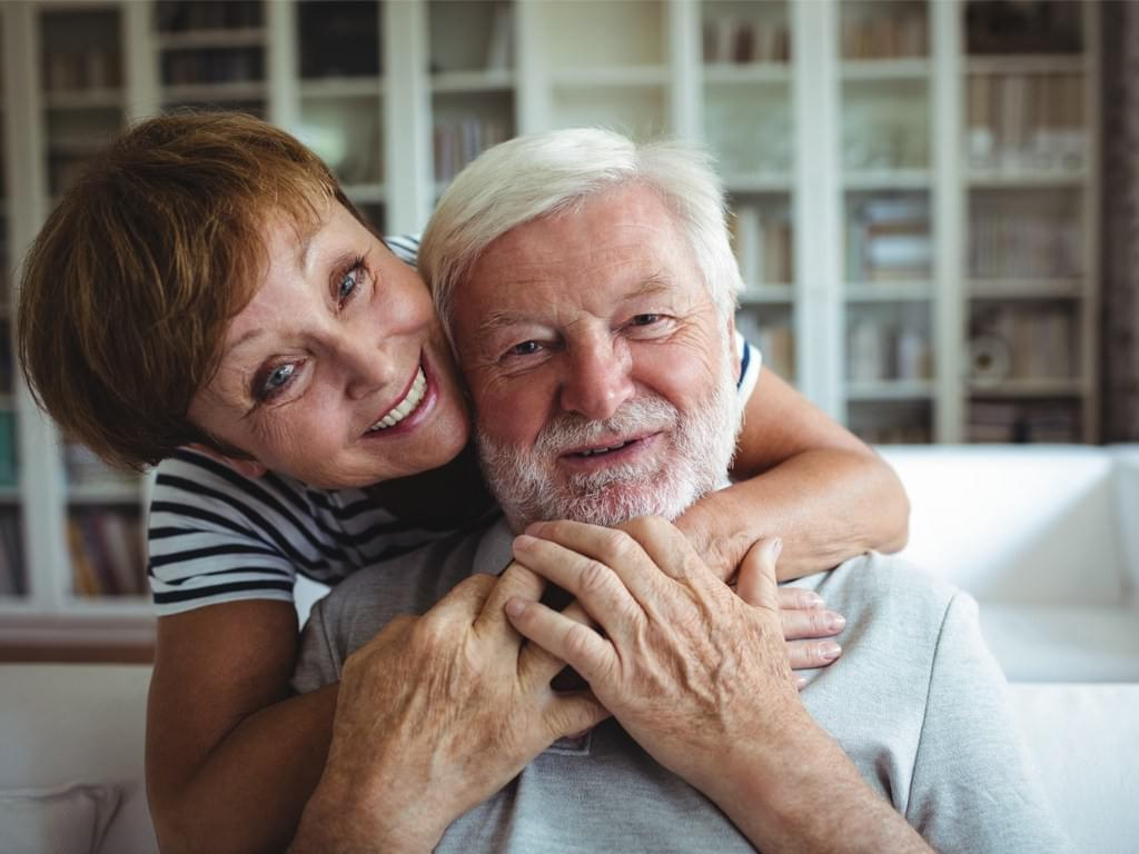 Woman in 60's hugging man on couch
