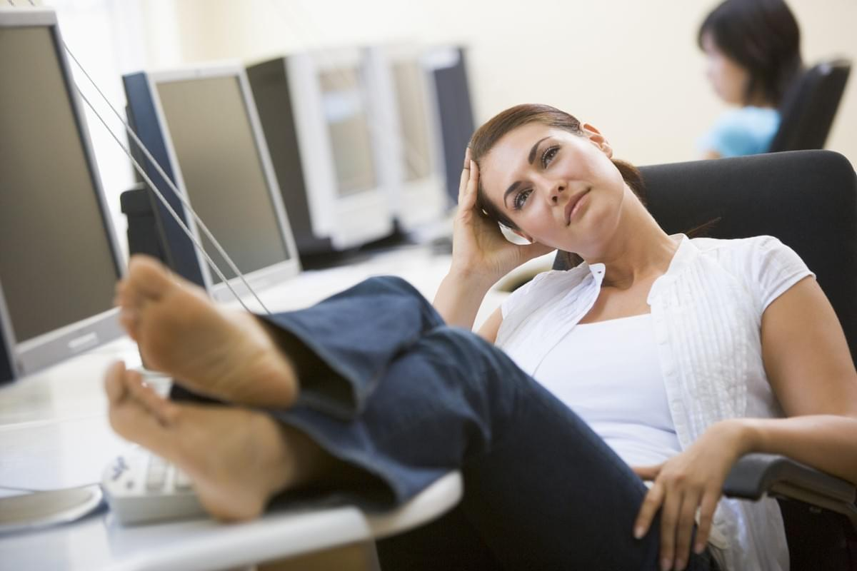 Woman in 30s with feet up on desk thinking