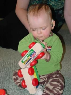 Deaf baby sitting on floor playing with a toy