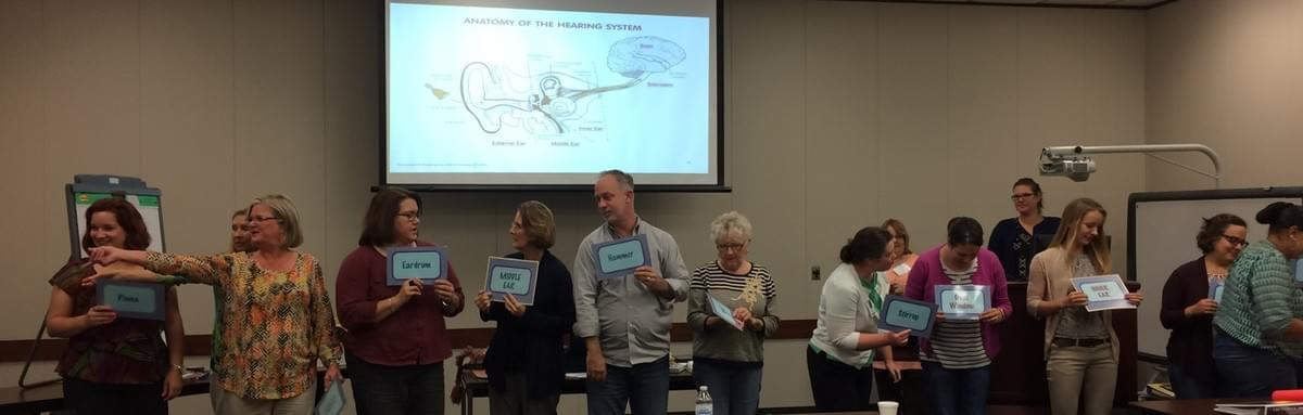 Trainees acting out the parts of the hearing system