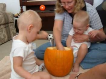 Adult with twins (toddler aged boys) exploring inside of pumpkin