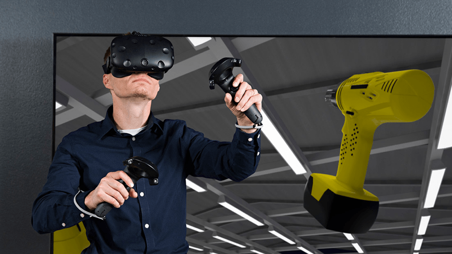 An image of a male wearing VIVE and two handles, controlling a virtual drill