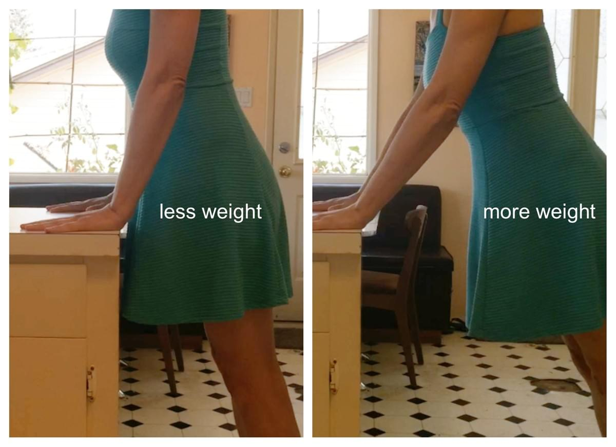 Almost vertical plank with hands supported on a counter illustrating how to add less weight by moving the feet closer to the counter or more weight into your wrists by stepping the feet further from the counter