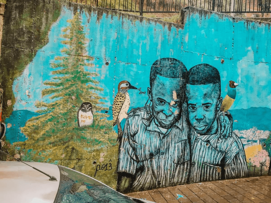 street art of 2 black boys with birds in the birds on their shoulders in comuna 13 Commune 13 San Javier in medellin